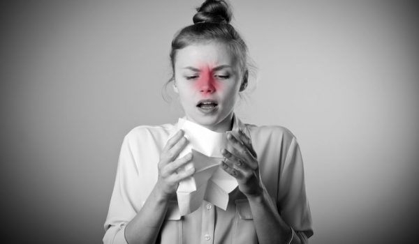 66356969 - young slim woman is sneezing. symptoms concept. grey and red colors.